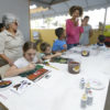 Crianças fazendo atividaddes de pintura com aquarela, com responsáveis e oficineira ao fundo