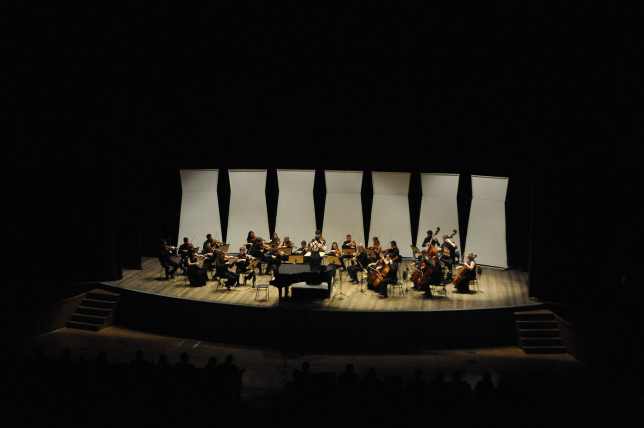 Foto do teatro Polytheama, somente com o palco e musicista da Orquestra iluminados, e com silhueta da plateia no escuro