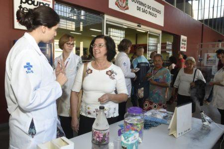 Mulher com uniforme branco fala com outra mulher. Na frente, mesa com acessórios