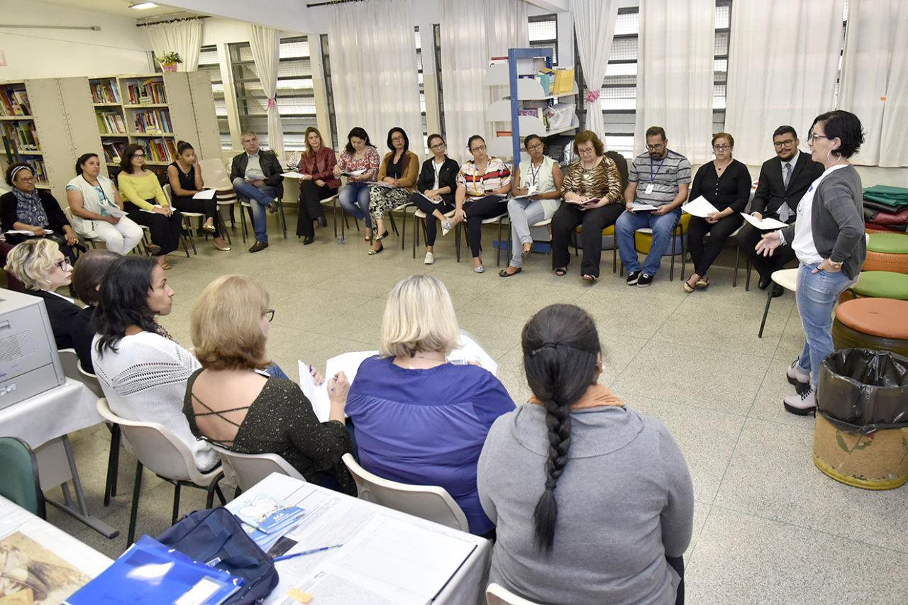 Sala de reunião, com participantes em semicirculo, dentro de sala de aula