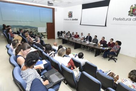 Auditório com pessoas sentadas assistindo a outras sentadas em mesa