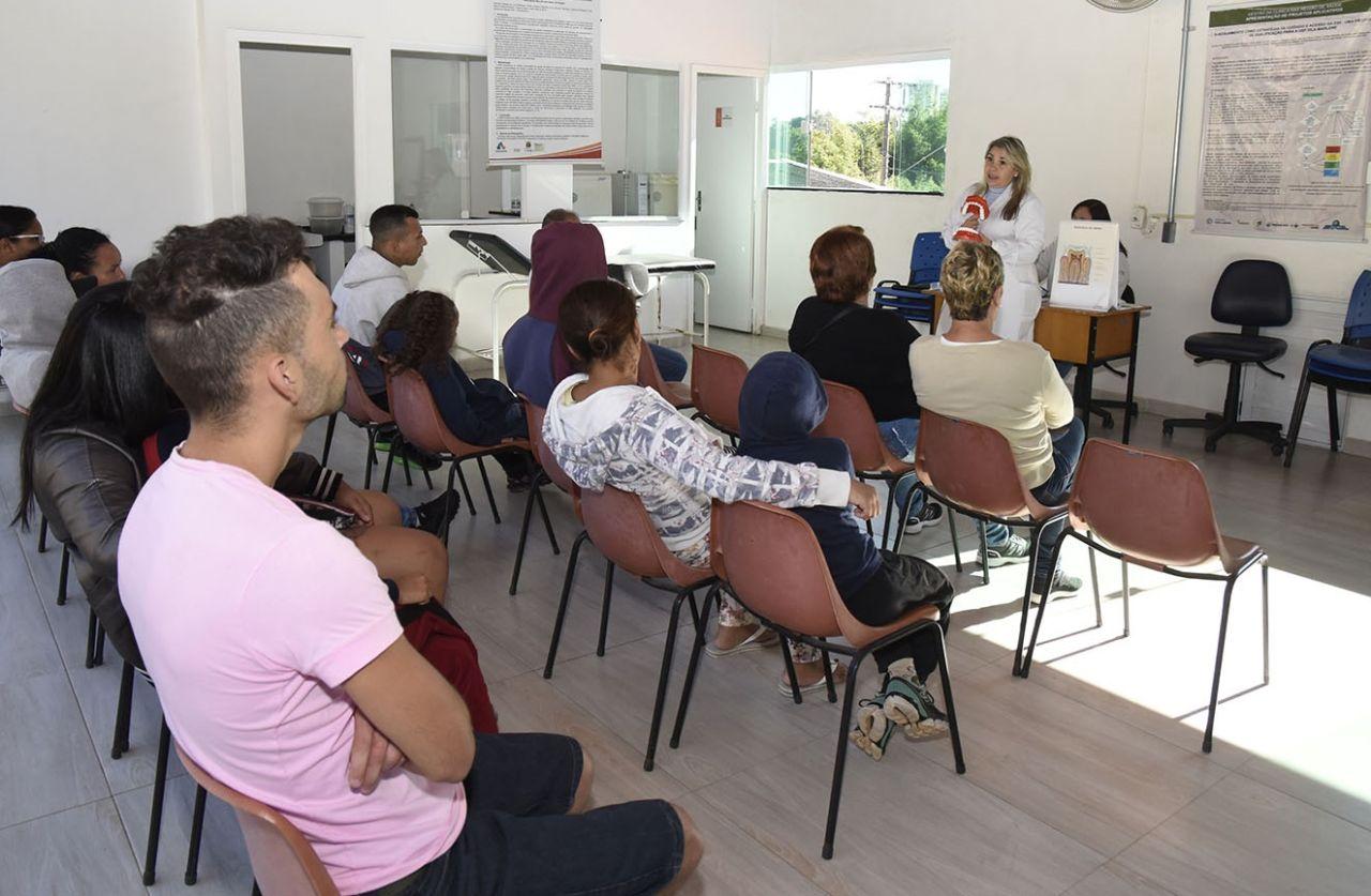 Pessoas sentadas assistem à enfermeira falar, em pé
