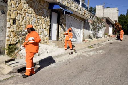 Dois varredores fazem limpeza em calçada