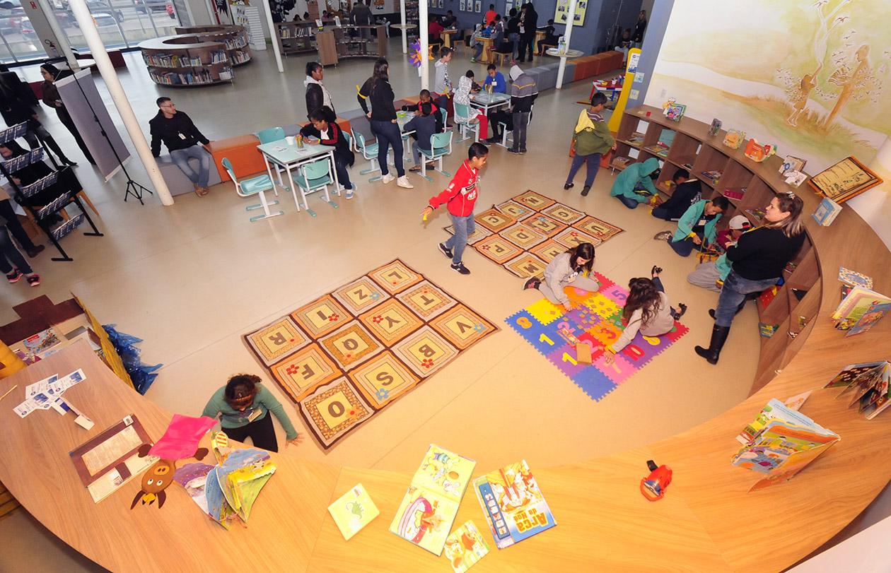 Foto do ambiente de brinquedoteca da Biblioteca, com crianças brincando, mexendo em livros e sobre tapetes interativos