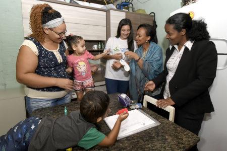 Quatro mulheres interagem com menina, com brinquedo feito de papel, com menino entretido sobre a mesa com tubos de tinta