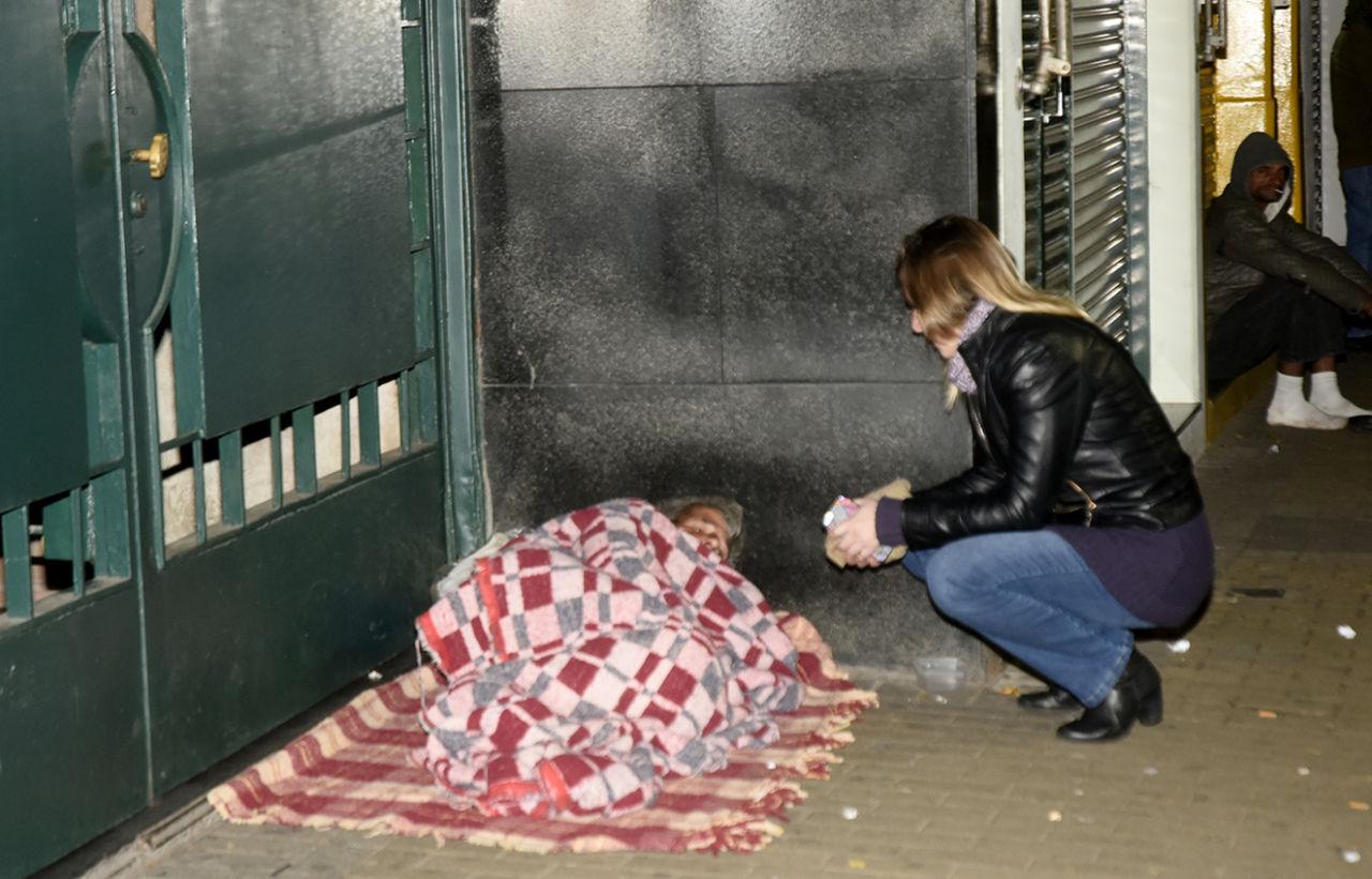 Mulher conversa com pessoa deitada em chão com cobertor