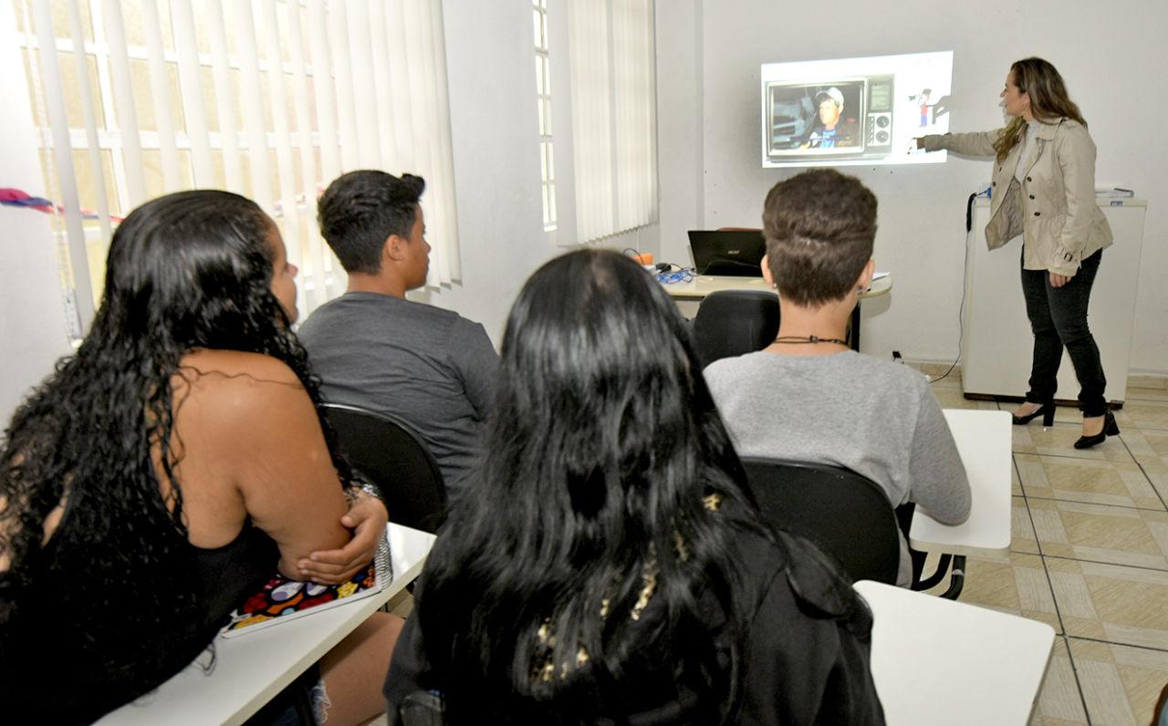 Sala de aula, com alunos jovens assistindo a uma apresentação, com mulher à frente da sala