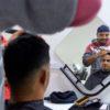 Homem corta o cabelo de outro em frente ao espelho