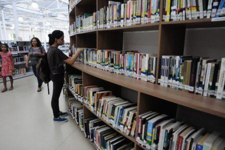 Mulher olha livros em estante