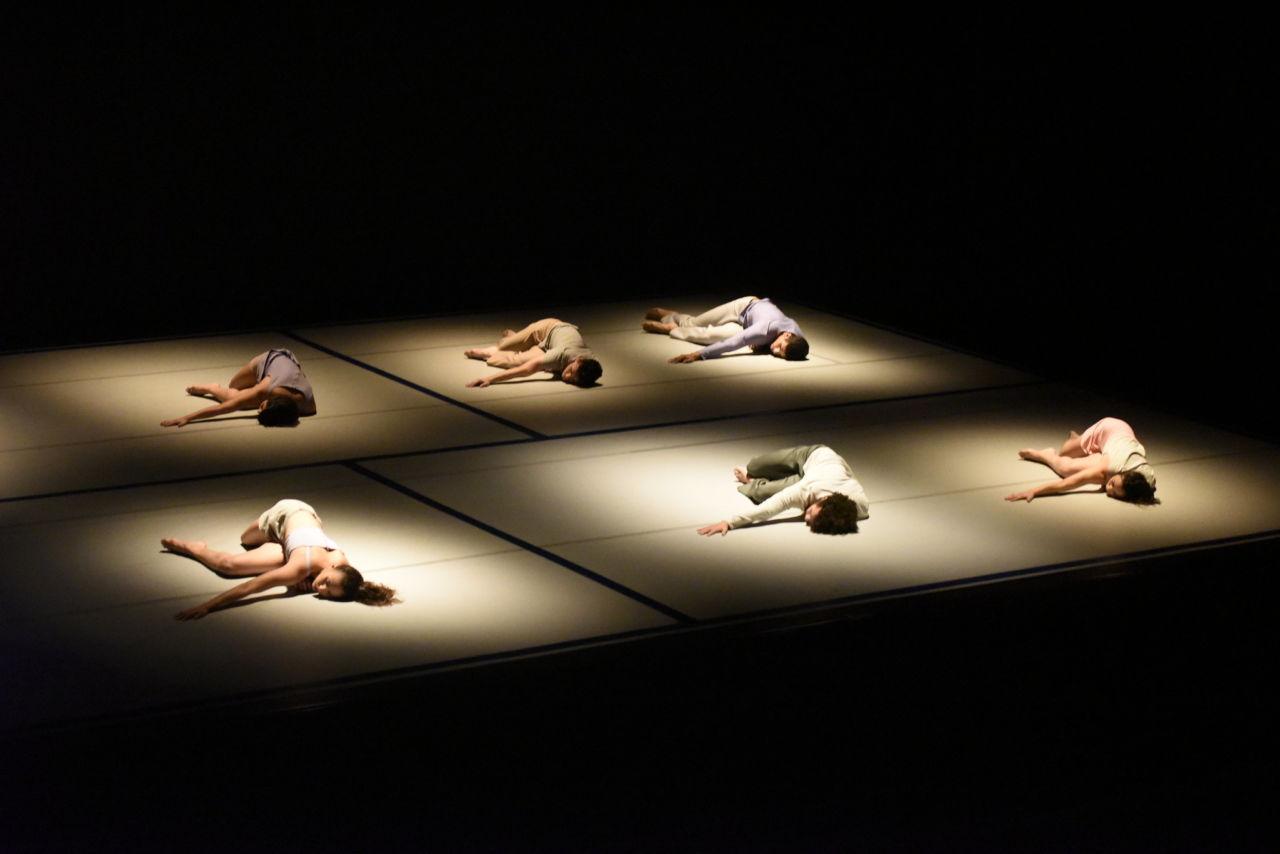 Palco do teatro no escuro, com focos de luz sobre bailarinos, que fazem performance deitados