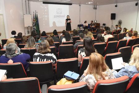 Foto de fundo de auditório, com pessoas sentadas, e palestrante sobre o palco