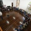 Foto vista do alto, em sala com chão de madeira, e grupo sentado em semicírculo, voltado para homem que dá a palestra