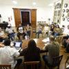 Pessoas sentadas em cadeiras em círculo em sala com relógios diversos na parede, porta de madeira e piano ao fundo