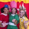 Três mulheres, com fantasias e vestidos infantis, em foto posada, com cortina de teatro ao fundo