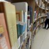 Prateleira de livros em primeiro plano, tendo ao fundo mulher observando os títulos