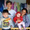 Em foto posada, mulher ao lado de duas crianças carrega bebê