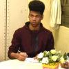 Jovem sentado, com caderno de notas sobre uma mesa com flores, fazendo anotações