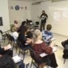 Em sala de aula, professor à frente com alunos sentados