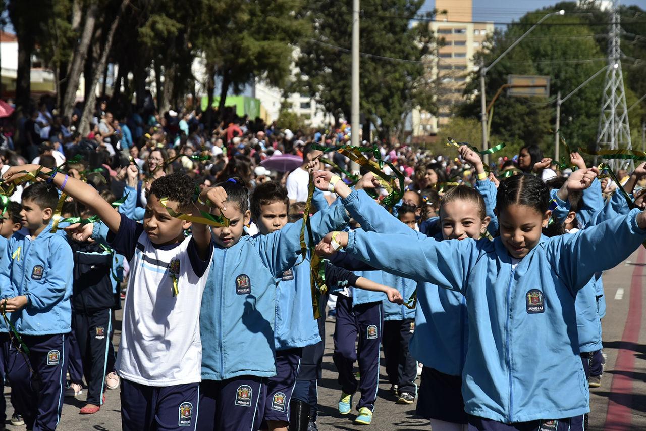 Crianças uniformaizadas e com faixas das cores da bandeira nacional em desfile no meio de uma avenida, com público atrás de gradis