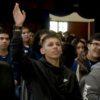 Menino levanta a mão em plateia, com outras pessoas sentadas