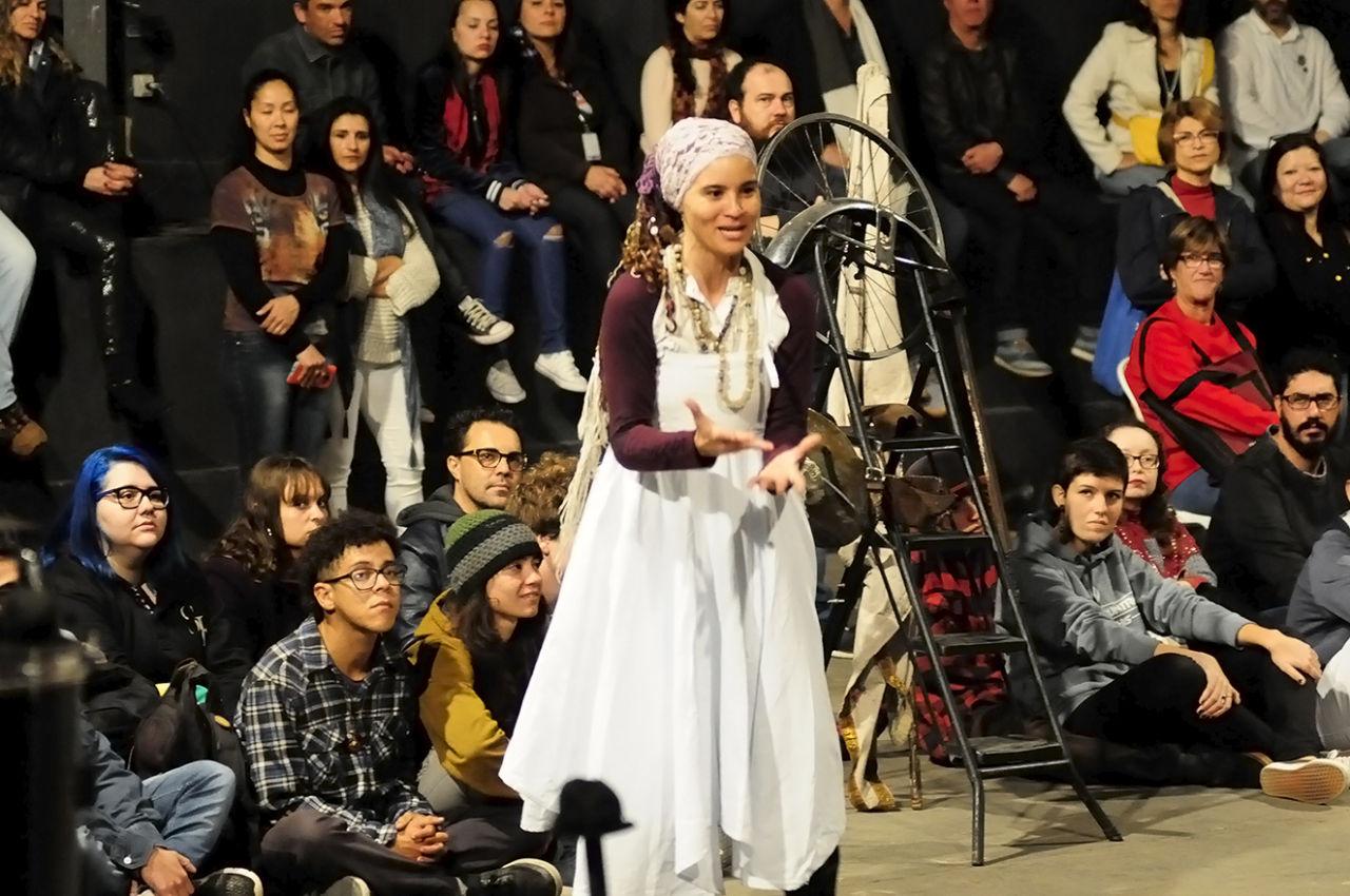 Mulher com vestido e cabelo coberto, durante apresentação, cercada pelos espectadores