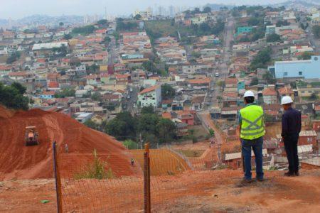 Técnicos vistoriam obra com bairro ao fundo