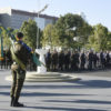 Militar segura bandeira do Brasil enquanto outros militares perfilados observam