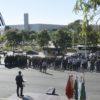 Praça vista do alto, com o prefeito, de costas, discursa a militares perfilados em formação, a bandeira do Estado de São Paulo listrada ao fundo
