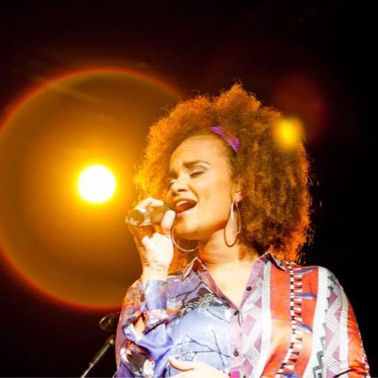 Mulher cantando, segurando o microfone, com os olhos fechados, com foco de luz ao fundo