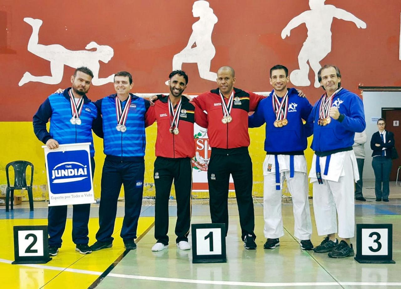 Foto posada da equipe de karatê com medalhas