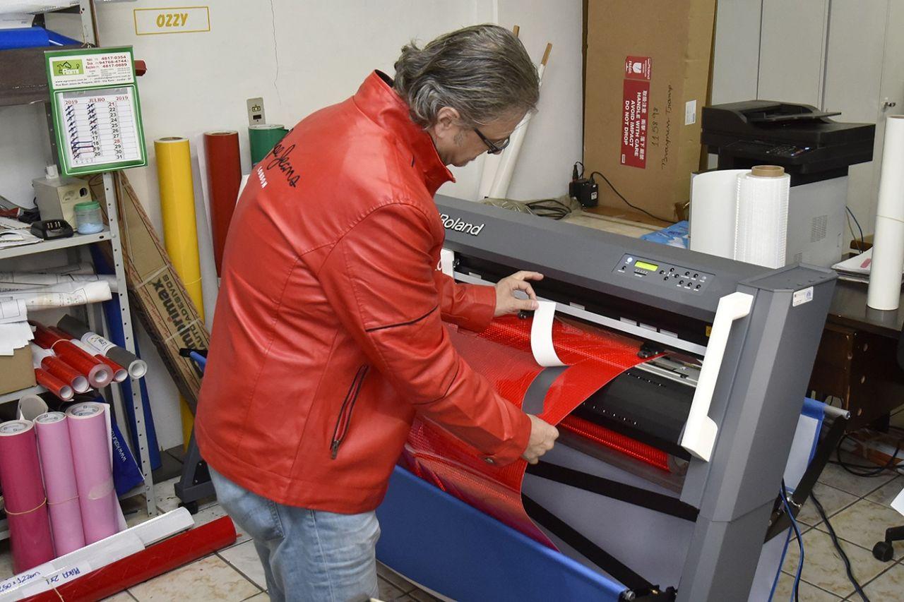 Homem manuseia máquina de placas