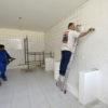 Homens reformando sala sem móveis