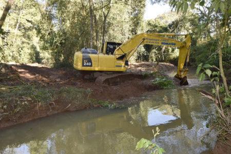 Trator trabalha nas margens de rio