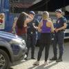 Duas guardas municipais com uniforme durante atendimento a duas mulheres de costas, com frente de viatura da Guarda e ônibus ao fundo, com dois guardas
