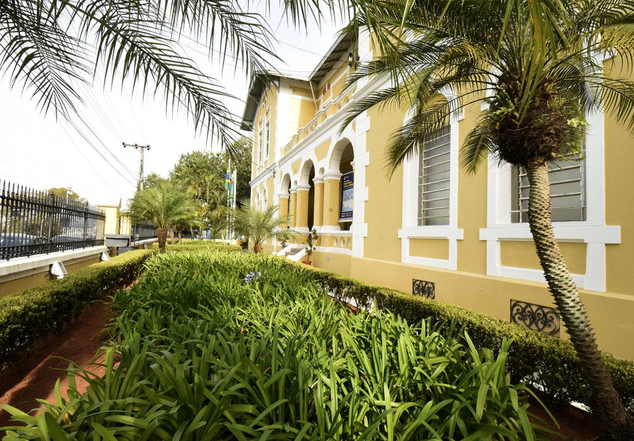 Fachada de prédio na transversal, com jardim à frente