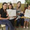 Foto posada de mães com as filhas, que expõem folhas em branco com testes de tintas naturais
