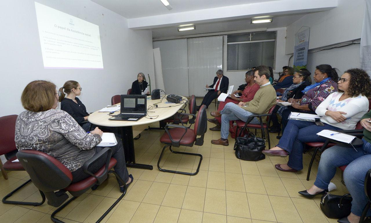 Sala de reunião, com pessoas sentadas, acompanhando apresentação em projetor na parede