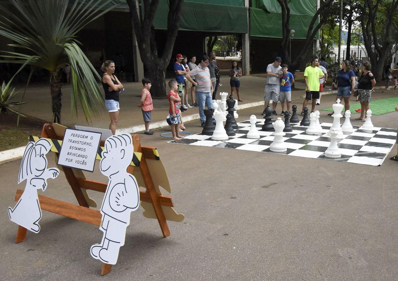 Xadrez em tamanho humano montado em rua do Parque da Uva, com crianças e adultos movendo as peças