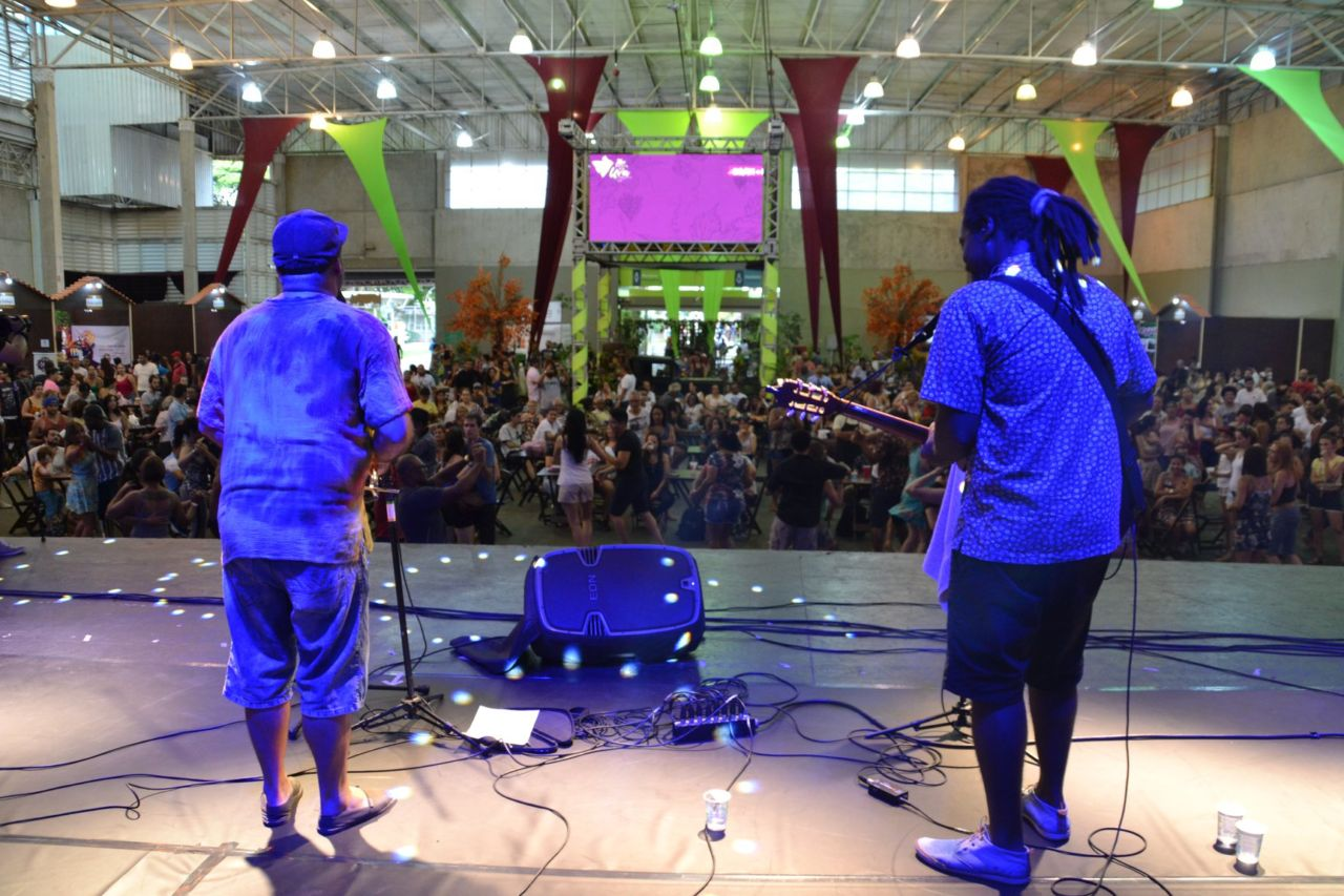 Foto de trás de palco, com dupla em apresentação de costas, e pavilhão com público assistindo