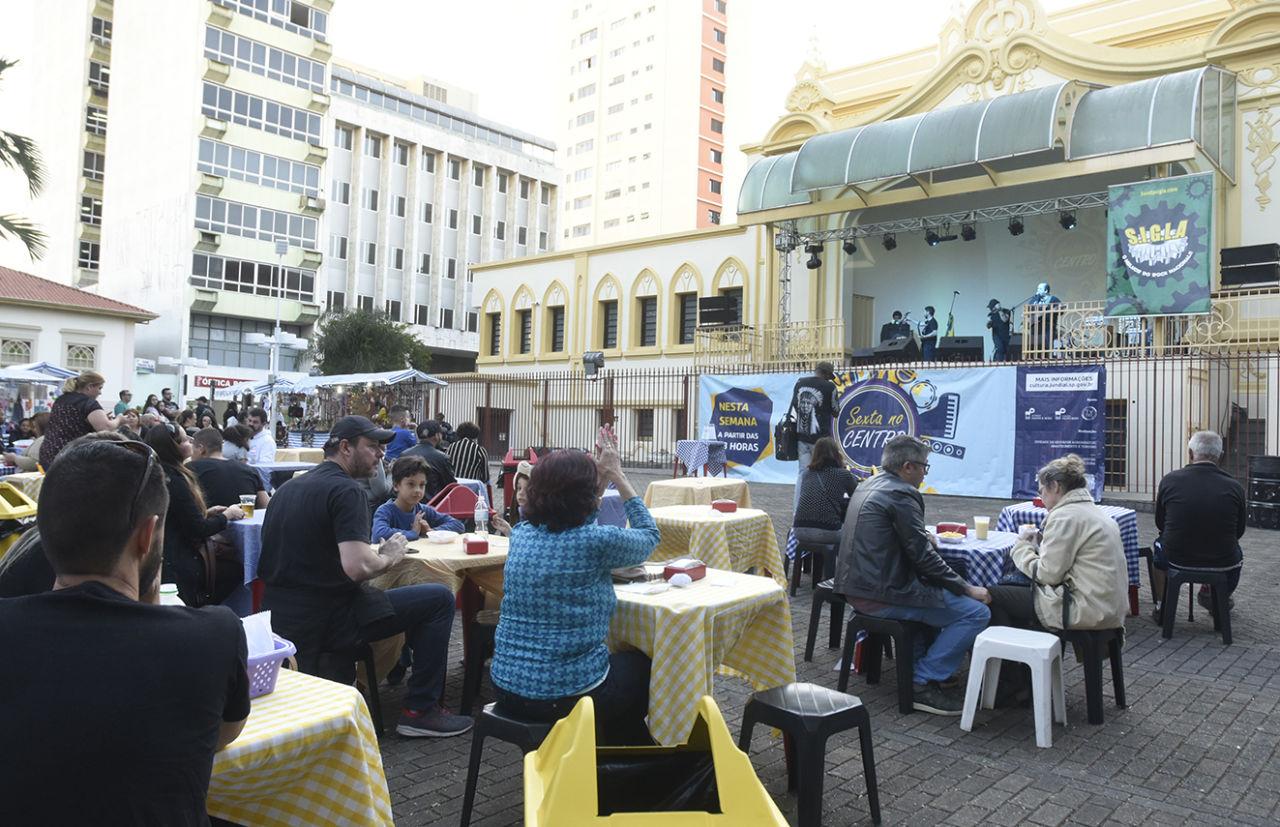 Praça com mesas montadas, pessoas sentadas, enquanto assistem a show de banda iluminadas com luzes no palco