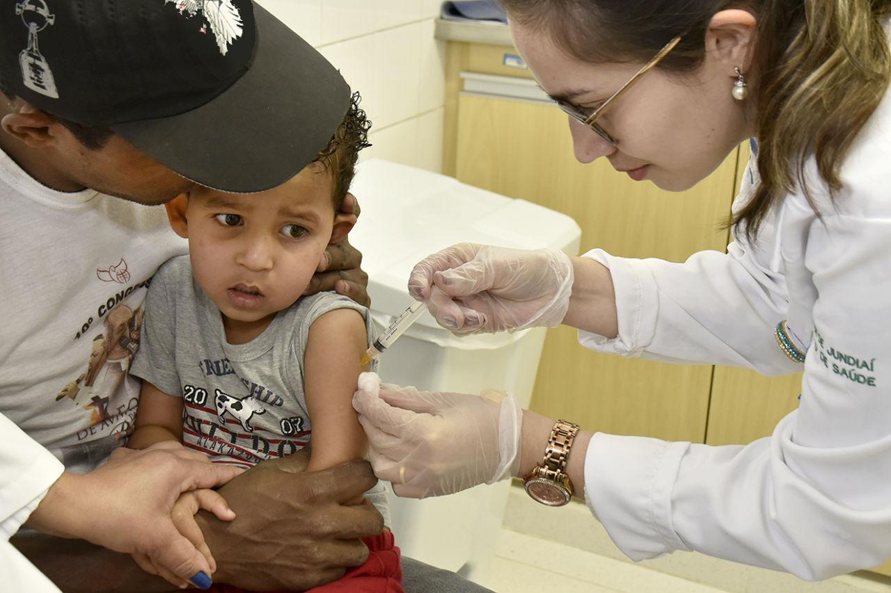 Criança recebe vacina no braço, no colo da mãe