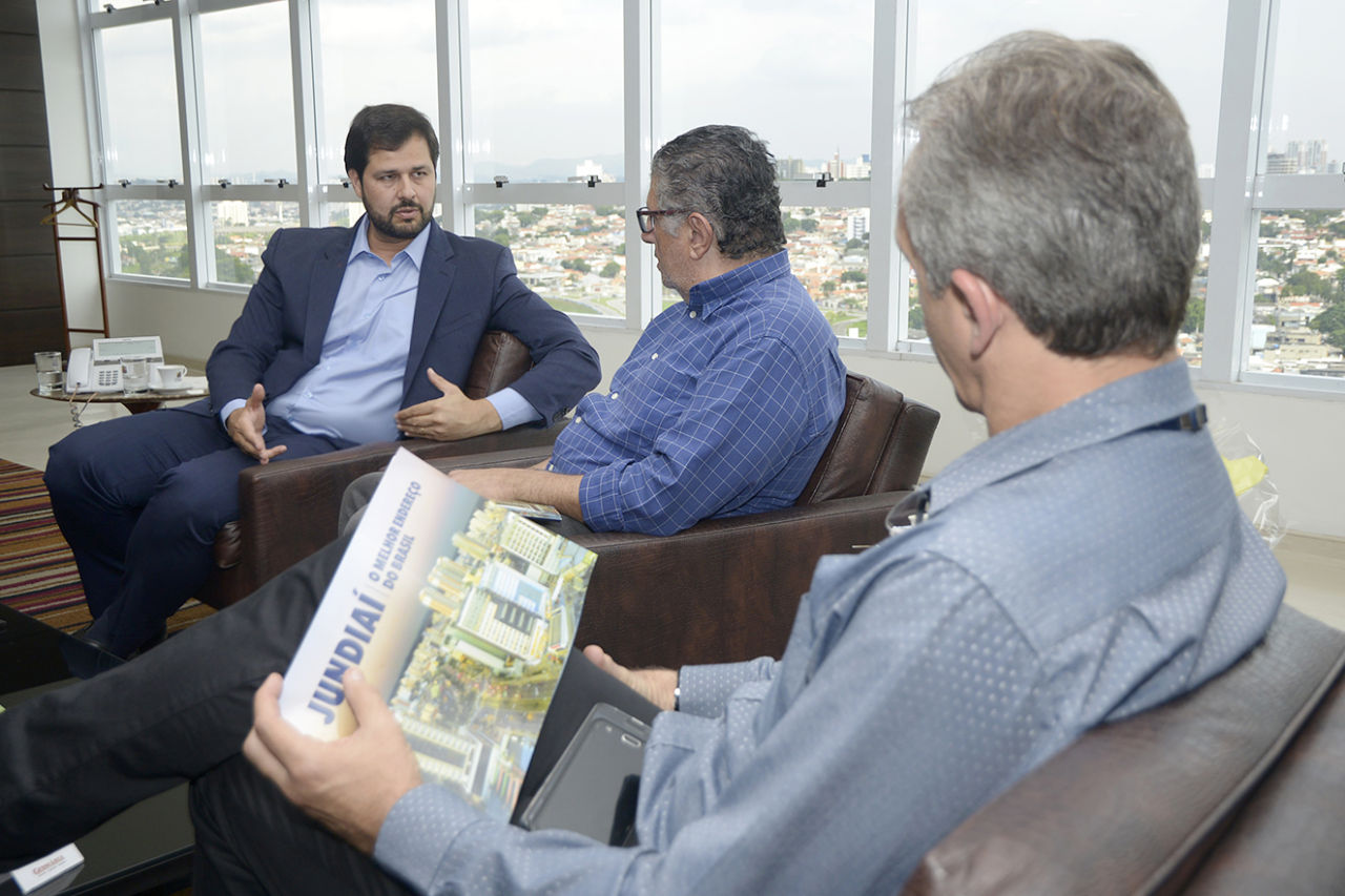 Prefeito conversa com empresários, sentados e com a vista de Jundiaí ao fundo