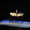Foito do palco do teatro no escuro, com bailarinos segurando um travesseiro gigante, com um bailarino em cima