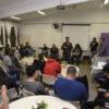 Sala de aula, com pessoas assistindo à apresentação de um palestrante à frente da sala
