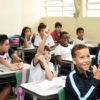 Sala de aula, com crianças sentadas em cadeiras dispostas em fileiras, com uma menina com a mão levantada pedindo a palavra