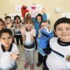 Crianças olha pra câmera e mostram as mãos