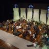 Foto do alto do palco do teatro, com músicos ensaiando
