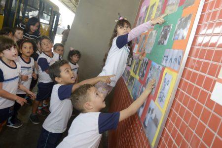 Crianças com uniformes mostram e olham fotos em painel