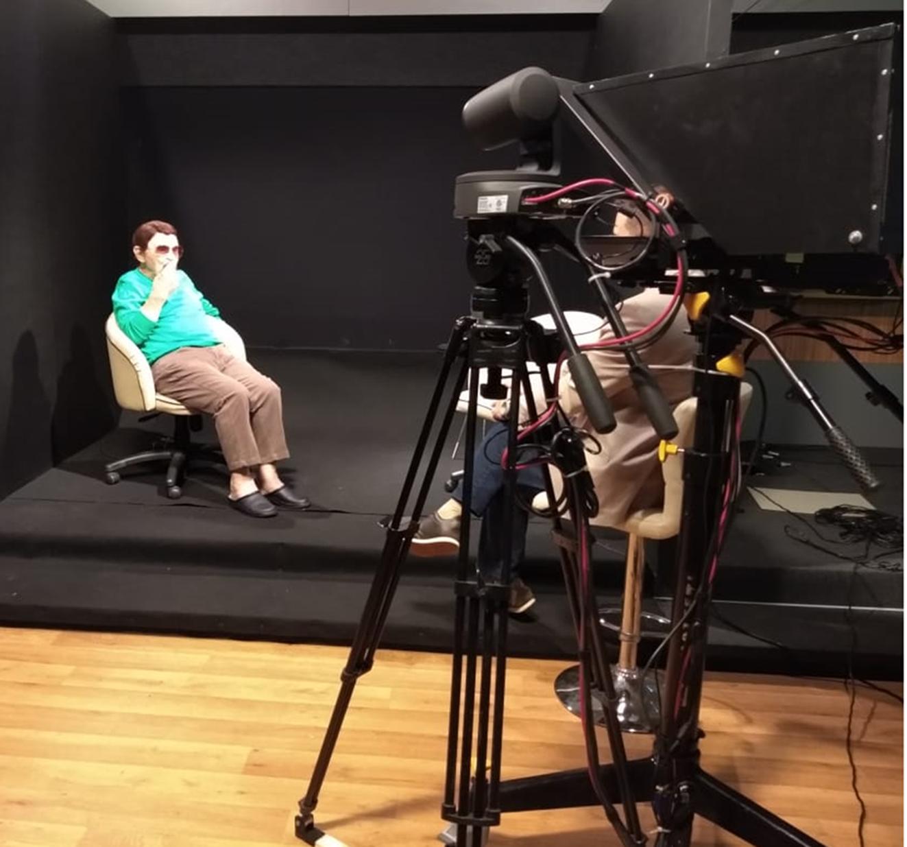 Câmera filmadora sobre tripé em primeiro plano, com dois homens sentados, conversando, em posição de entrevistador e entrevistado