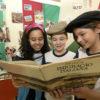Três crianças seguram livro